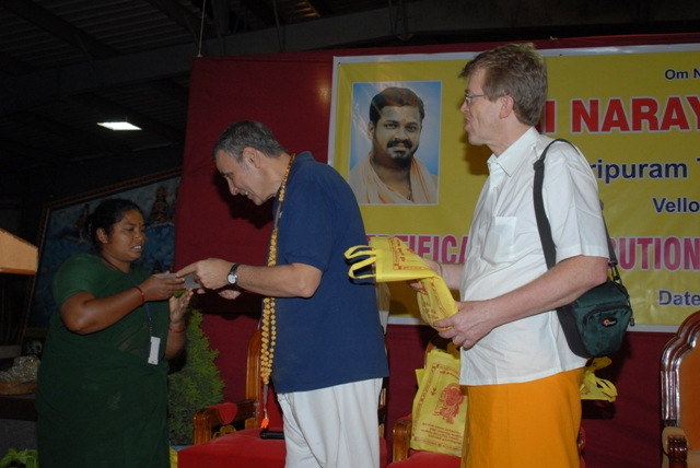 Stan and Jim presents a certificate and a bag of prasadham to a member of the Peedam staff