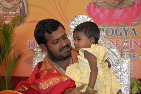 Amma holds a baby (a Gift of Life recipient)