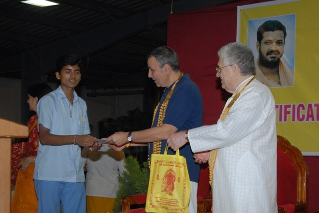 Stan and Phillip presents a certificate and a bag of prasadham to a member of the Hospital staff