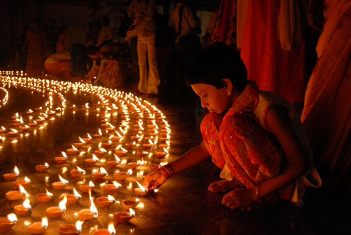 Devotees help to light the diyas