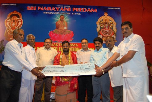 Beloved Amma and invited guests present the cheque to the school officials