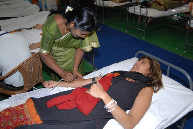 A devotee donates blood in spite of the pain