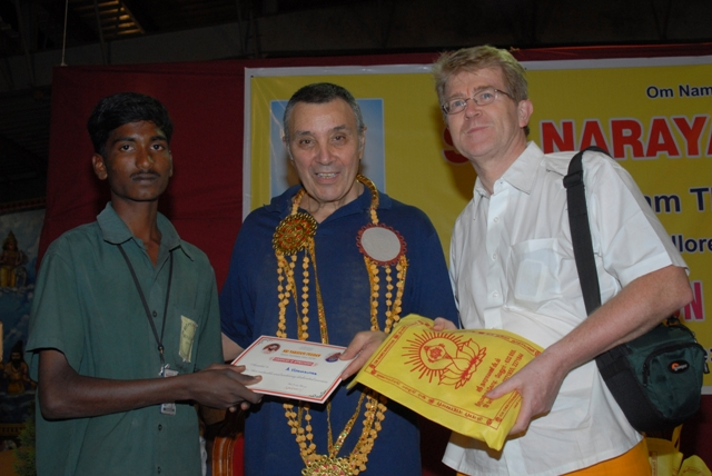 Stan and Jim present a certificate and a bag of prasadham to a member of the Peedam staff