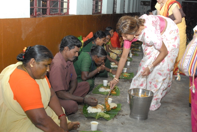 Devotee serves food to the Appreciation certificate recipients