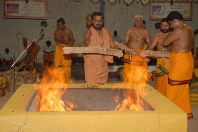 Sri Sakthi Amma adds the pieces of wood to the fire