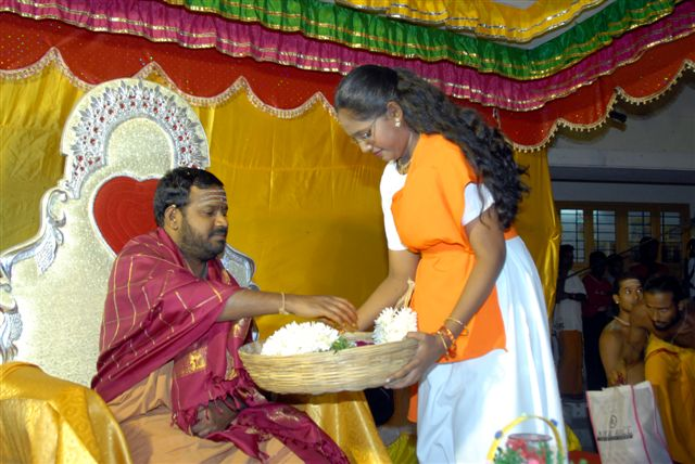 Young student present Beloved Amma with a garland