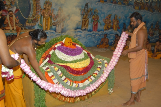 Sri Sakthi Amma adds the flower garlands to the fire