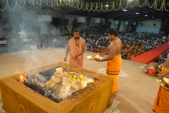 Sri Sakthi Amma adds an offering to the fire