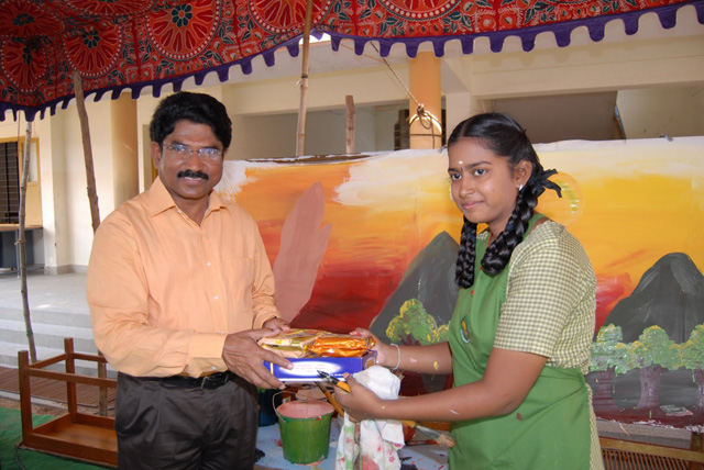 Student artist receives a gift from the Chief Guest