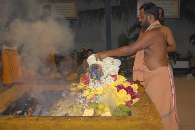 Sri Sakthi Amma adds the garlands of fresh flowers to the fire
