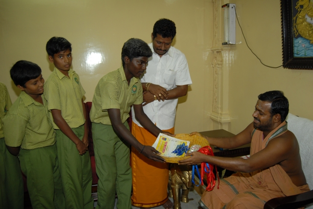 Students receive blessed pens from Sri Sakthi Amma