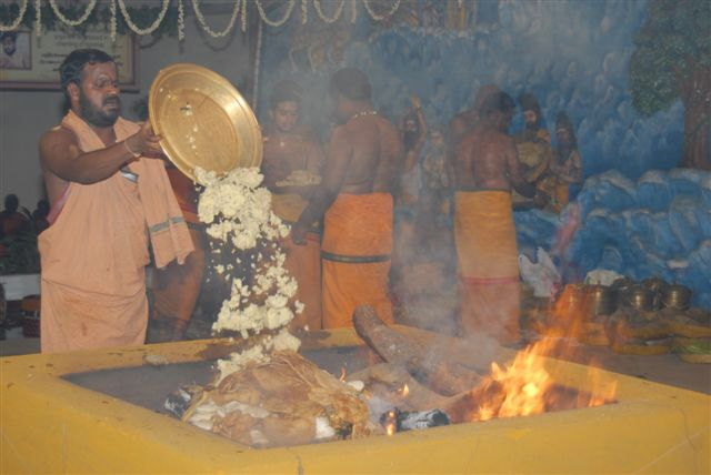Beloved Amma adds an offering to the fire