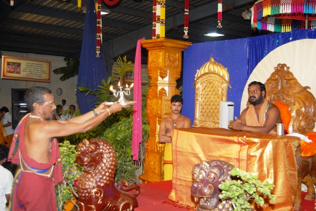 Temple priest performs arathi to Beloved Amma