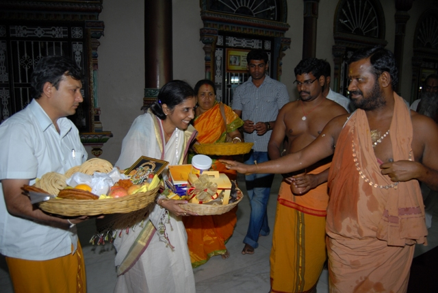 Beloved Amma blesses the offerings from devotees after the yagam