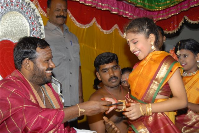 Young students receive a token from Beloved Amma after their dance performance