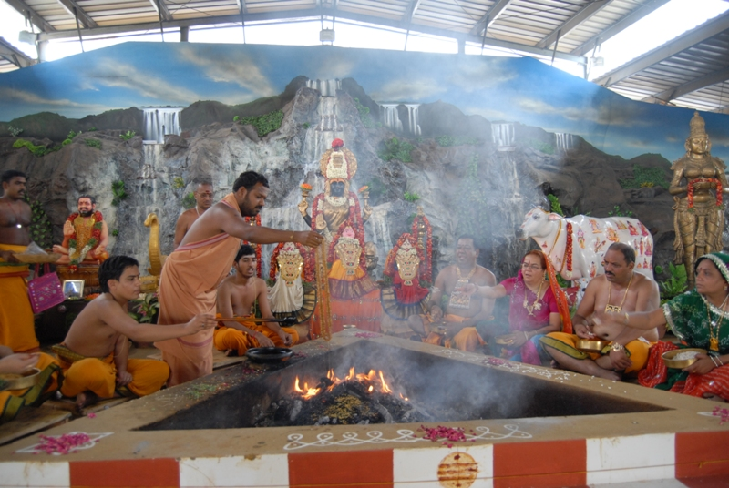 Beloved Amma adds an offering into the fire