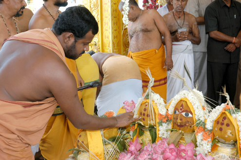 Amma adds a dot from the yagam to each of the kumbams