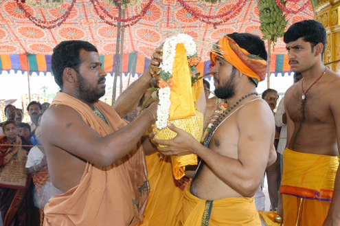Amma gives the priest the kalasam