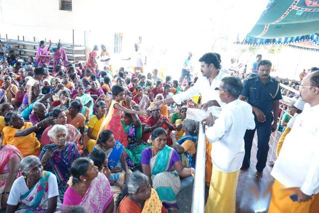 Shri Suresh distributes the packets of juice (drinks)