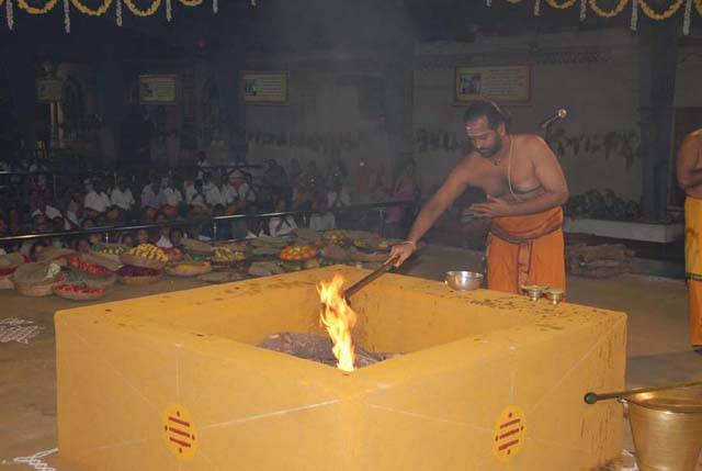 Priest offers ghee into the Fire