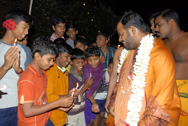 Young villagers welcome Beloved Amma with lighted candles