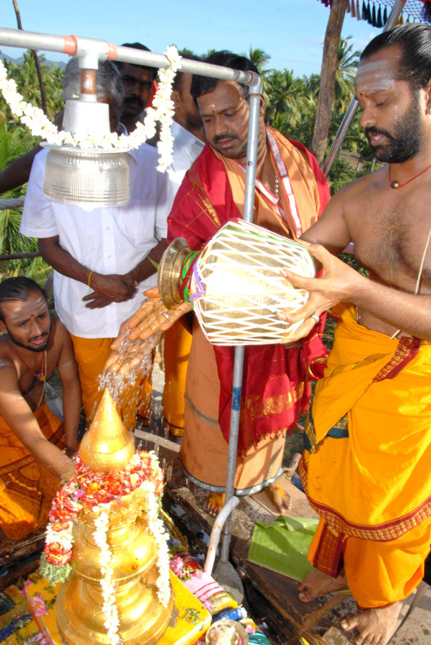 Beloved Amma and the priest perform abhishekam to consecrate the temple