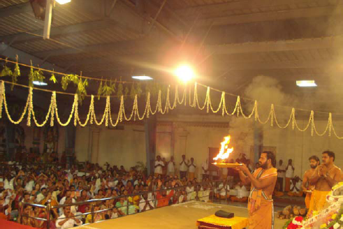 Amma faces the gathering with the arathi