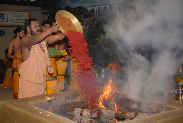 Beloved Amma adds an offering of kumkum into the fire