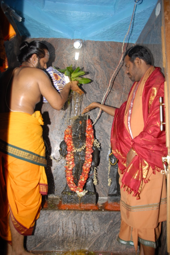 Priest performs the abhishekam on the Murthi