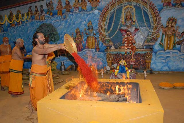 Priest adds the kumkum offering into the Yagam