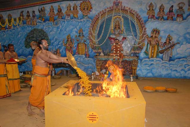 Priest adds the tumeric offering into the Yagam