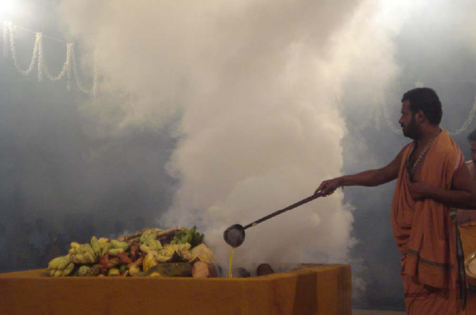 Amma adds ghee to the Fire