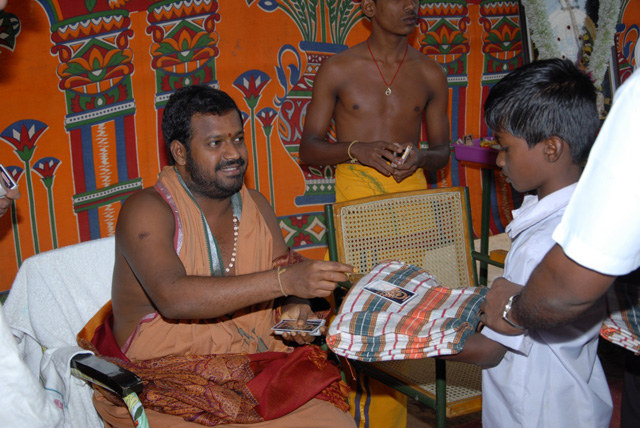 Beloved Sri Sakthi Amma gives a dhoti to the young boys