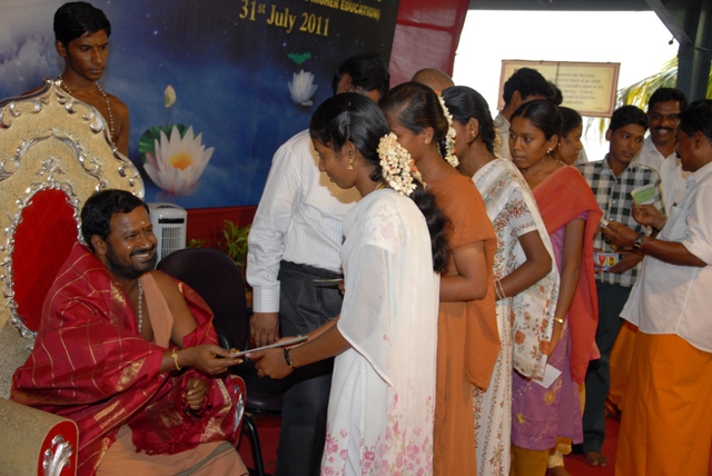 Students receive cheques from Sri Sakthi Amma