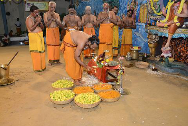 The priest performs the aarathi