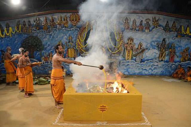 The priest adds ghee to the yagam