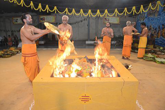 The priest adds an offering into the yagam