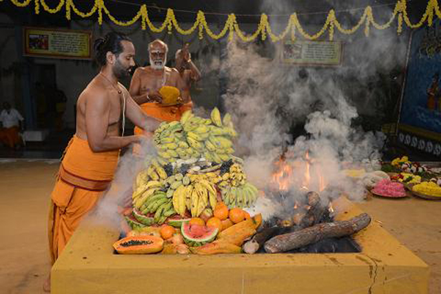 The priest adds the bananas into the yagam